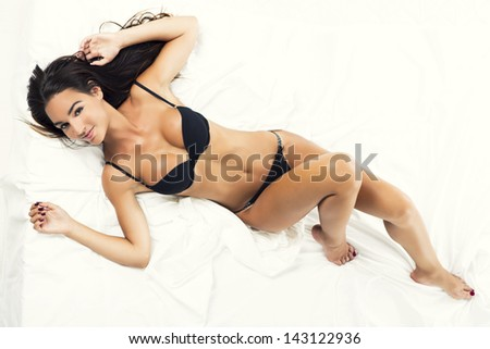 Beautiful and sexy woman with a black lingerie lying on bed, isolated on white background - stock photo