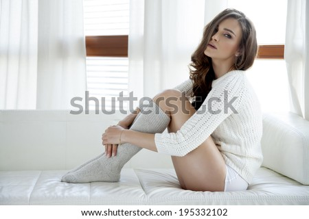 Beautiful and sexy young adult sensuality brunette woman in white sweater and grey socks on the white sofa in window on luxury apartment - stock photo