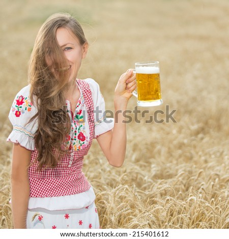 Beautiful and sexy young blond woman drinking beer in wheat field background. focus on face. soft daylight - stock photo
