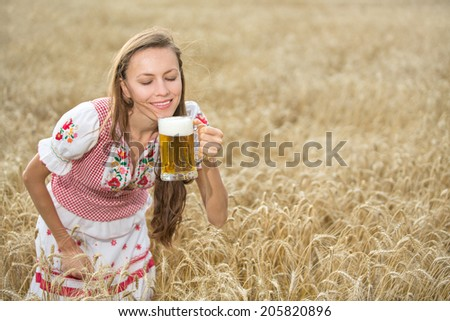 Beautiful and sexy young blond woman drinking beer in wheat field. soft daylight. copy space