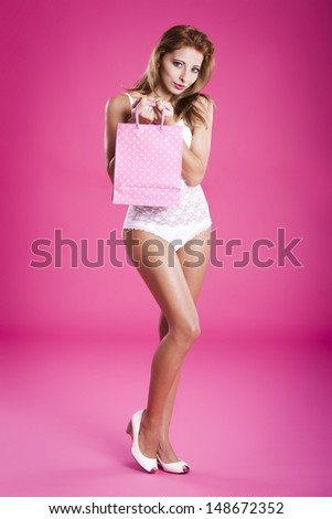 Beautiful and sexy young woman in lingerie holding a shopping bag, over a pink background