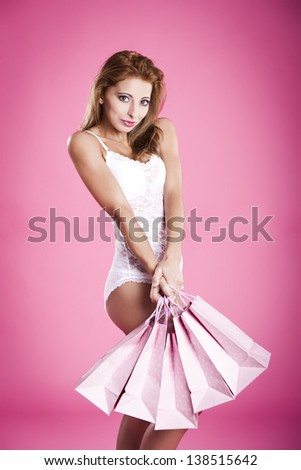 Beautiful and sexy young woman in lingerie, holding shopping bags, over a pink background - stock photo