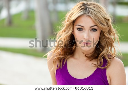 Beautiful and sexy young woman outdoors in a park setting. - stock photo