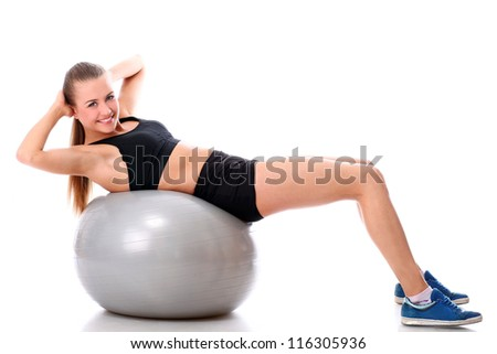 Beautiful and smiling woman doing abs exercises with fitness ball over white background - stock photo