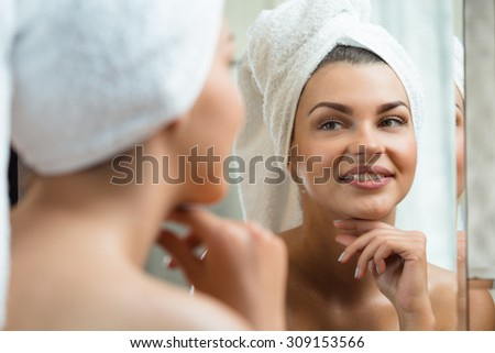 Beautiful and smiling woman looking at the mirror - stock photo