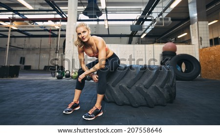 Beautiful and strong young woman sitting on a big tire after her exercise. Woman taking break after crossfit workout at gym. - stock photo