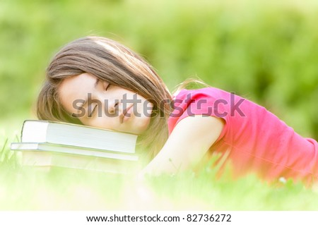 beautiful and tired young student girl lying on green grass, pile of books under her head, her eyes closed. Summer or spring green park in background - stock photo