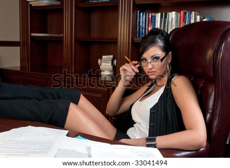 Beautiful and very sexy secretary working after hours. - stock photo