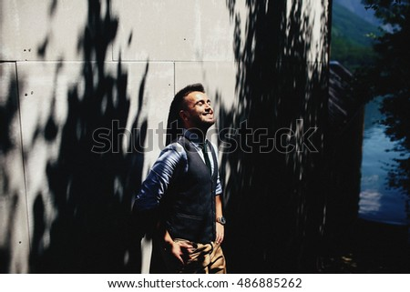 beautiful and young boy standing near the wall