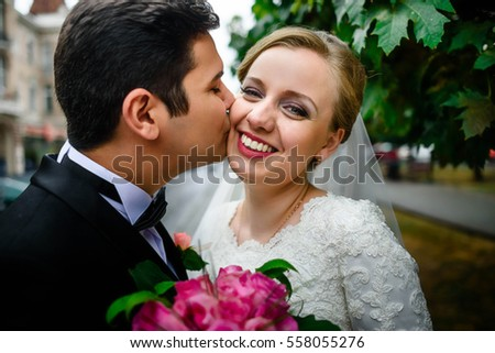 beautiful and young bride and groom kissing on the street