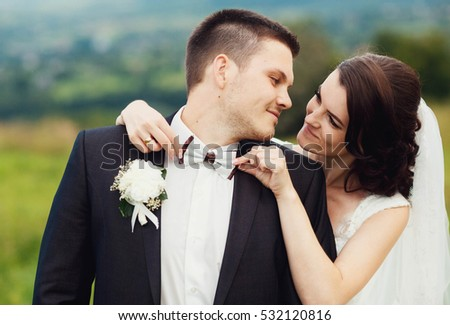 beautiful and young bride and groom standing together outdoors