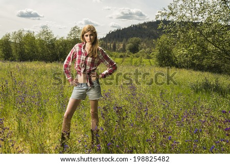 Beautiful and young girl posing outdoors in the grassy field in red flannel shirt and jeans shorts - stock photo