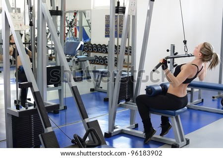 Beautiful and young woman in motion working out in the gym on lat machine. - stock photo