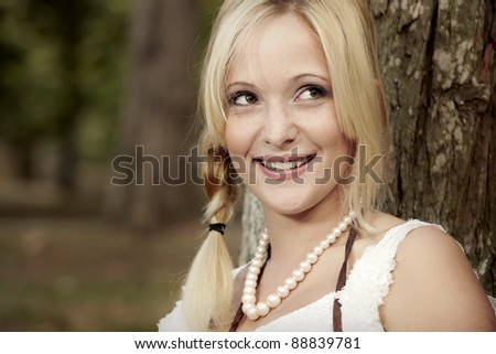 Beautiful anf happy girl sitting close to a tree and enjoying the day - stock photo