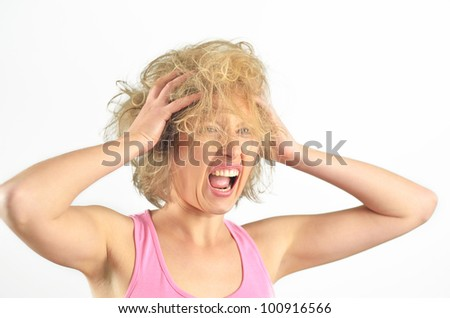 Beautiful angry girl pulling her messy hair on isolated background - stock photo