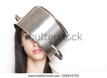 Beautiful annoyed girl using a steel pot like a hat - stock photo
