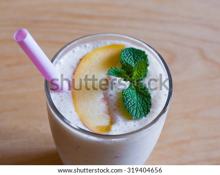 Beautiful appetizer peach fruit smoothie. Yogurt cocktail. Close up. Natural detox. Liquid ice cream. Rustic nature style.