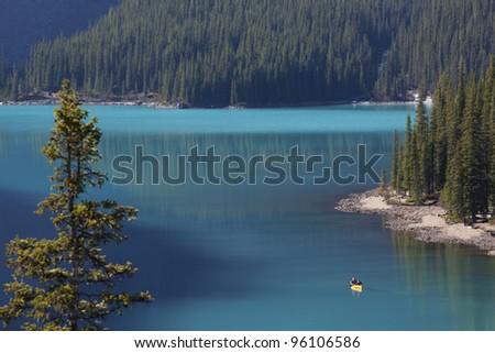 Beautiful aqua colored lake with a canoe in water. - stock photo