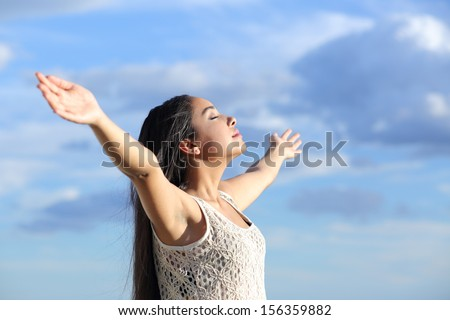 Beautiful arab woman breathing fresh air with raised arms with a cloudy blue sky in the background          - stock photo