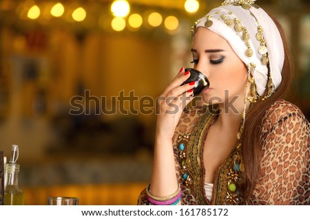 Beautiful Arabian model drinking coffee  - stock photo