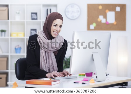 Beautiful Arabic business woman working on computer. Woman in her office,shallow depth of field - stock photo