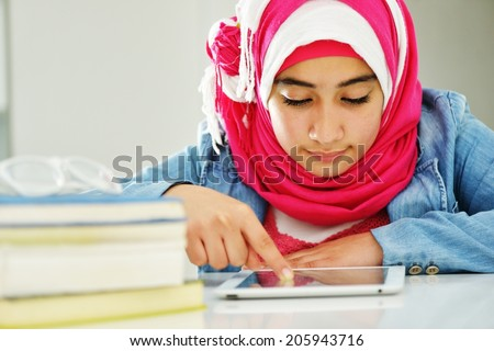Beautiful Arabic Muslim girl reading on college - stock photo