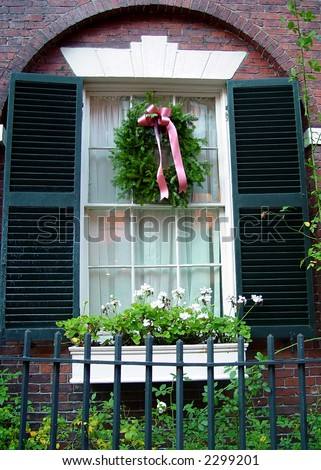 beautiful arched window frame with shutters and christmas wreath, flower box and old wrought iron fence in boston on beacon hill