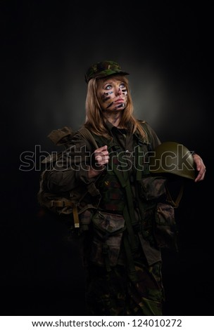 Beautiful army girl hold backpack and helmet, soldier woman in a military uniform over black background
