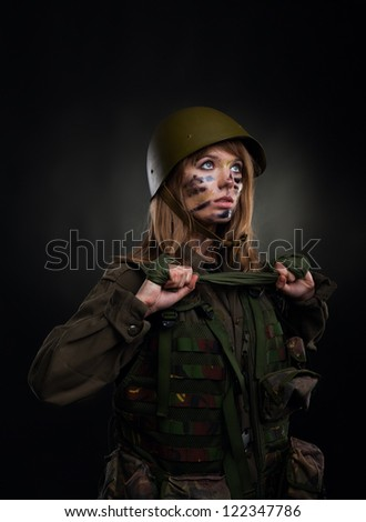 Beautiful army girl, soldier woman in a military uniform over black background