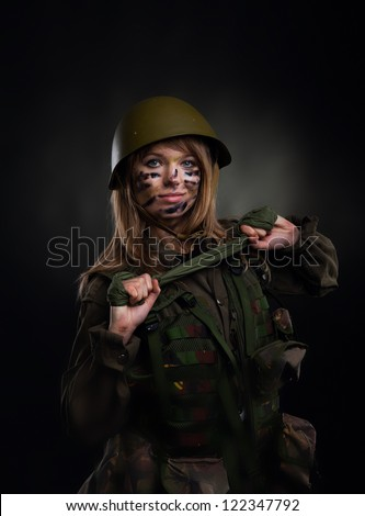 army girl, soldier woman in a military uniform over black background ...
