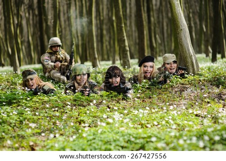 Beautiful army girls with gun  outdoor in the forest - stock photo