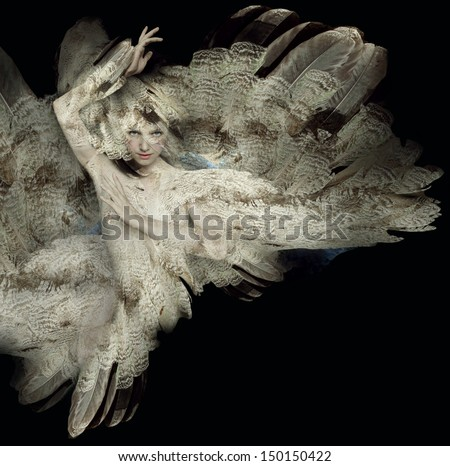 Beautiful artistic portrait of a girl with plumage on black background - stock photo