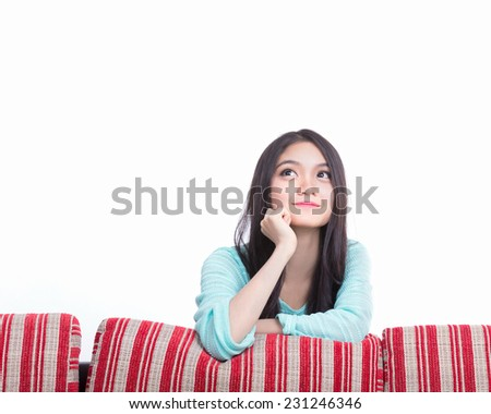Beautiful asia thoughtful woman looking up with red sofa - stock photo