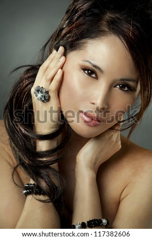 beautiful asian brunette wearing jewellery and fashin dress on dark background - stock photo