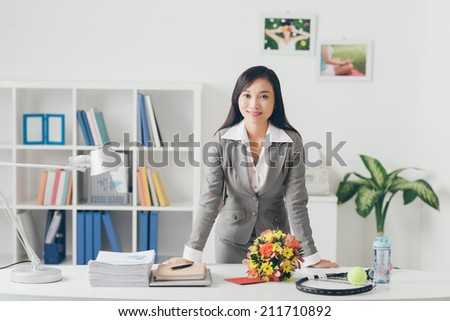 Beautiful Asian business lady at her work place - stock photo