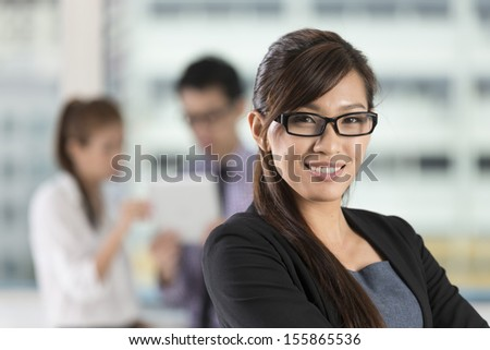 Beautiful Asian business woman standing with her staff in background