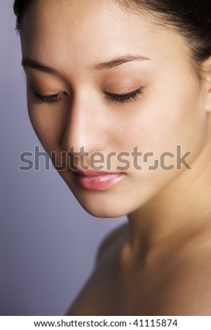Beautiful asian-caucasian mix young woman on purple background looking down, looking straight - stock photo