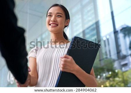 beautiful asian chinese business woman shaking hands in modern city work office - stock photo