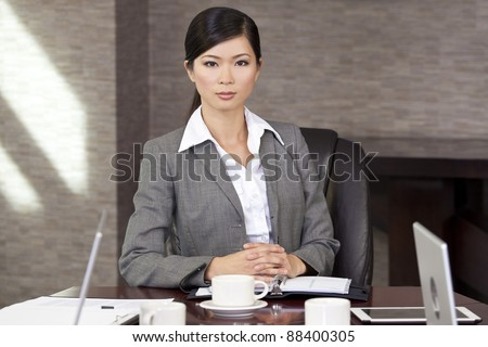 Beautiful Asian Chinese Woman or businesswoman sitting at a boardroom table - stock photo