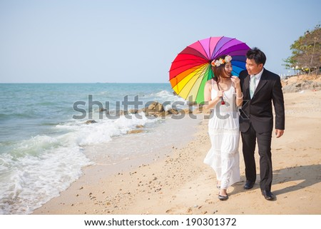 Beautiful asian couple on the beach in wedding dress