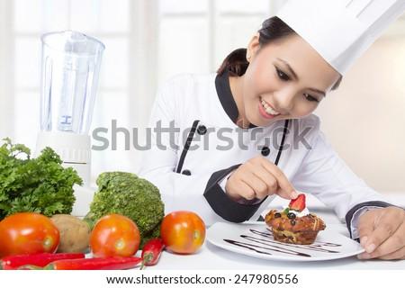beautiful asian female chef garnishing in the kitchen - stock photo