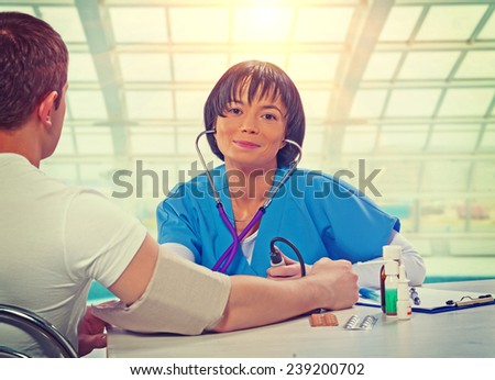beautiful asian female doctor sitting at the table with patient measuring blood pressure smiling and looking at camera instagram stile