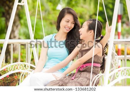Beautiful asian female family swinging in the garden - stock photo