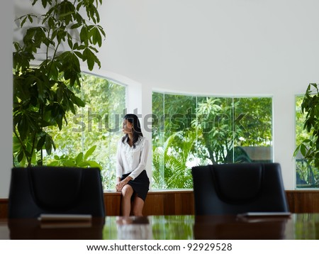 Beautiful Asian female manager looking out of the window in office. Front view, copy space - stock photo