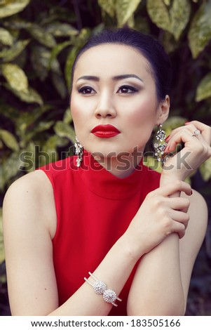 Beautiful asian female portrait with red dress and lips sitting on the green floral background - stock photo