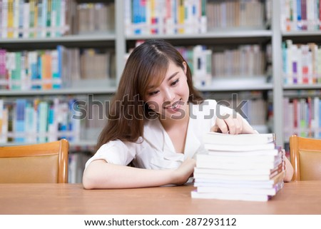 Beautiful asian female student portrait and books in library with bookshelf as background.