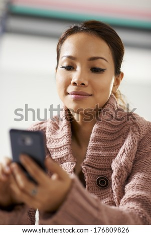 Beautiful asian girl chatting and text messaging on mobile phone - stock photo