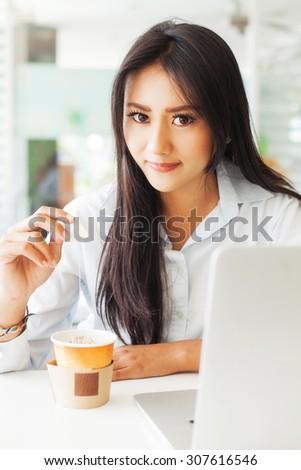 beautiful asian girl drinking tea  in a cafe - stock photo