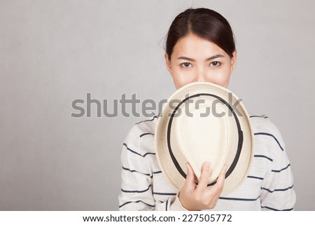 Beautiful Asian girl hold  a  hat close her mouth on gray background