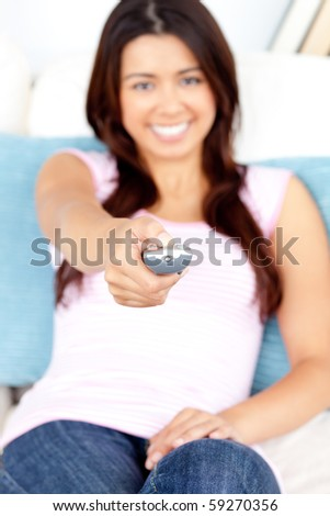 beautiful asian girl holding a remote sitting in her living room - stock photo